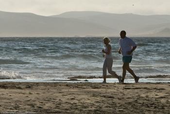 Father-daughter joggers on Morro Strand State Beach, Morro Bay, CA